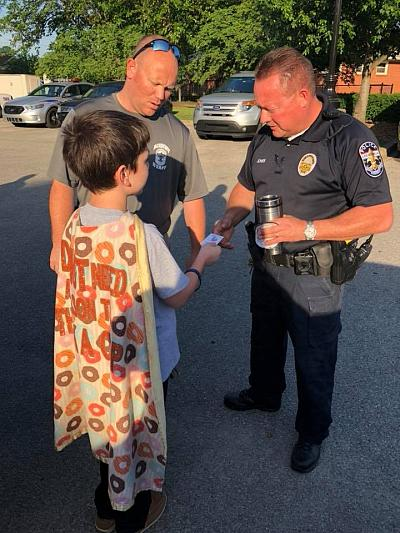 """Donut Boy"" Tyler Carach wears a cape on his deliveries. Here he is bringing doughnuts to officers in Louisville, Ky."