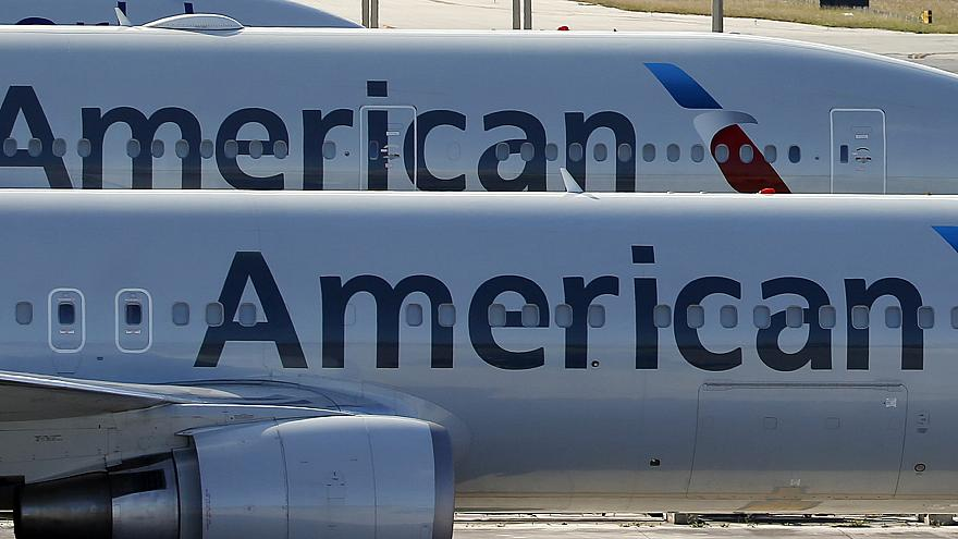 Image: A pair of American Airlines jets are shown parked on an airport apro