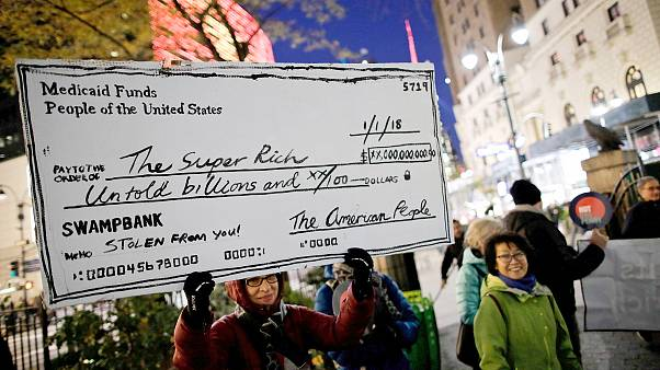 Image: Demonstrators take part in a protest against tax cuts for rich peopl