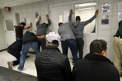 Immigration and Customs Enforcement (ICE), officers frisk undocumented immigrants after detaining and bringing them to an ICE processing center on April 11, 2018 at the U.S. Federal Building in lower Manhattan.