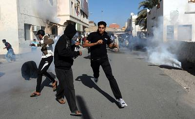 Protestors run for cover after police fired tear gas canisters to disperse them in the village of Diraz, northwest of Bahrain, on Feb. 14, 2011.