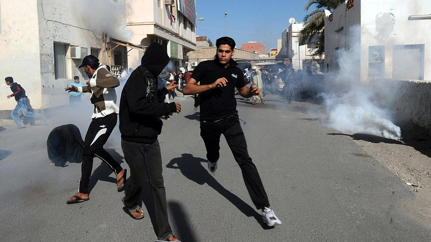Image: Bahraini protestors run for cover after