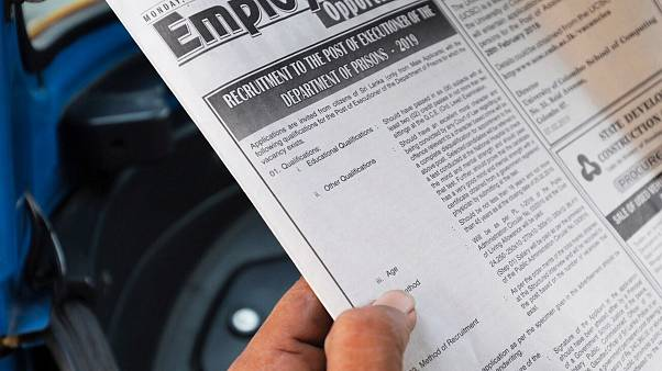 Image: A man reads an advertisement of the vacancy for hangmen on a newspap
