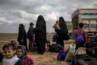 Civilians wait at a makeshift checkpoint after fleeing ISIS from the Syrian city of Bagouz on Feb. 9, 2019.