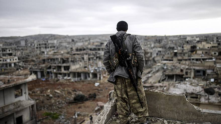 Musa, a 25-year-old Kurdish marksman, stands atop a building as he looks at