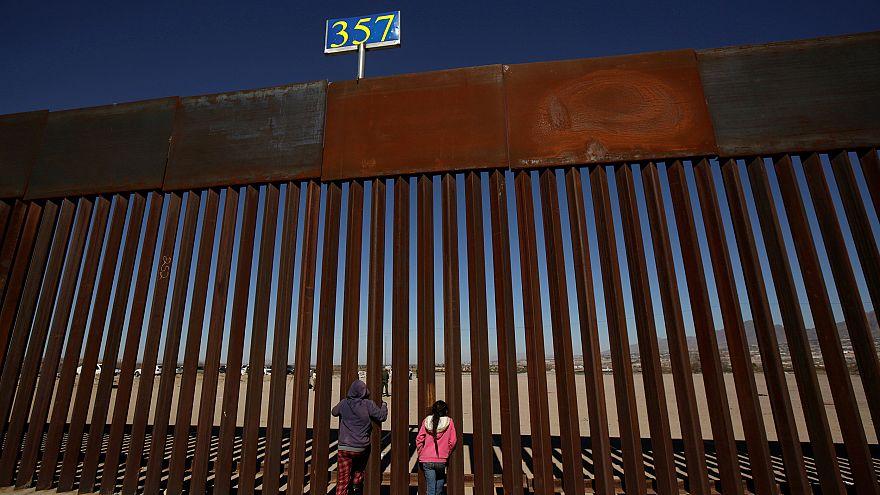 Image: Children peek through the border fence at Anapra neighbourhood in Ci