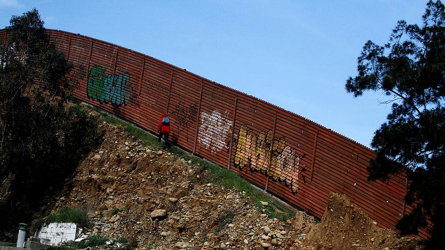 Image: A person walks along the U.S.-Mexico border fence in Tijuana on Feb.