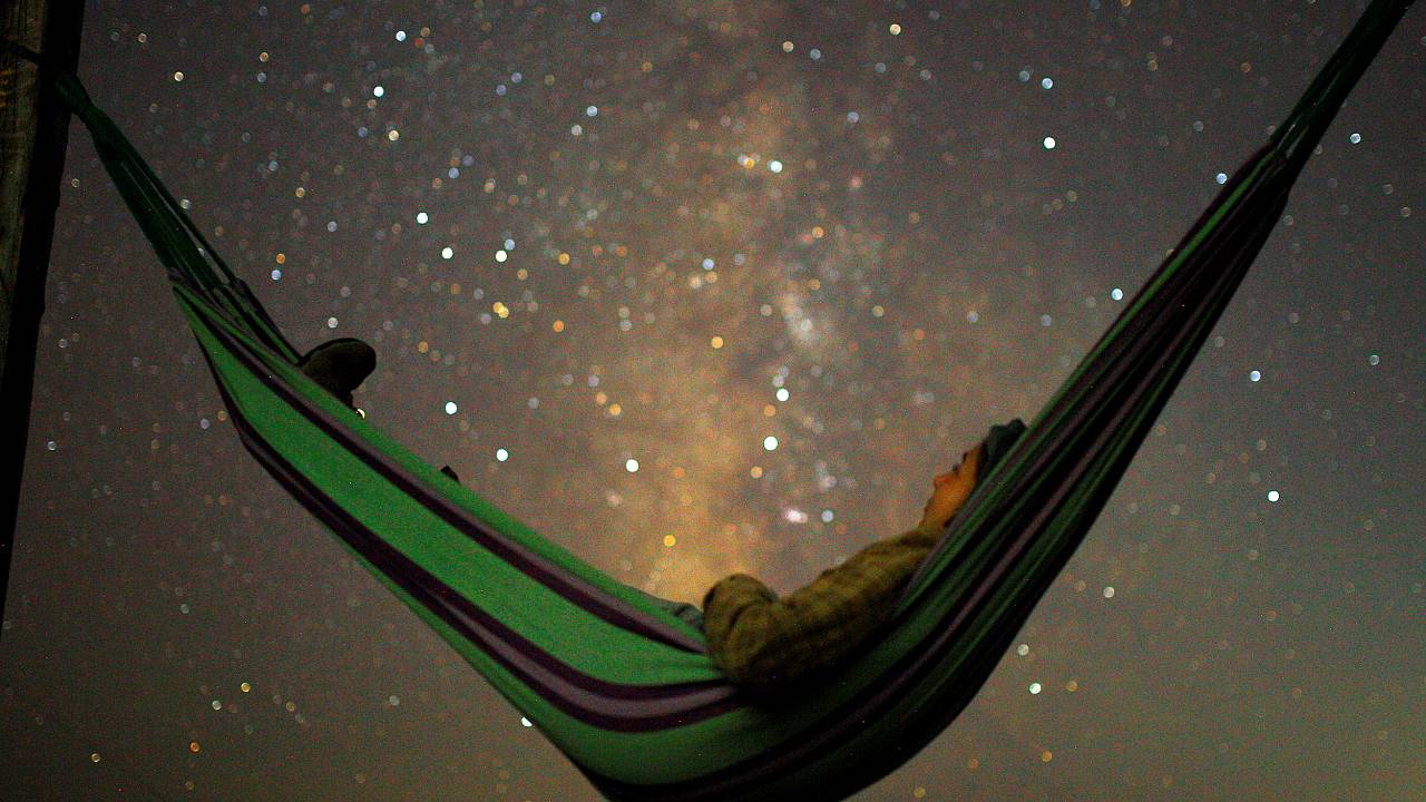 A girl lies in hammock as she looks at the milky way during the peak of Per