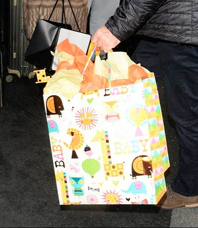 A member of Amal Clooney\'s entourage carried a bag full of baby gifts.