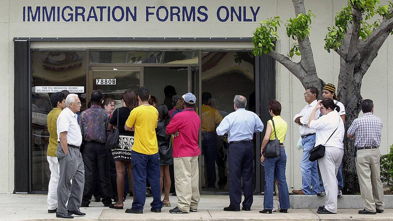 Image: A line forms near the entrance of the Immigration