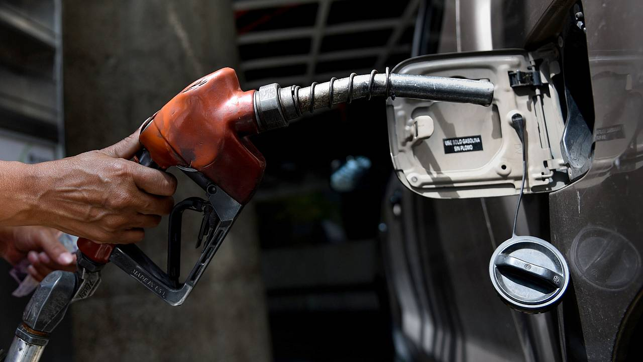 Image: An employee pumps gas into a car in Caracas, Venezuela, on Aug. 17,