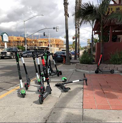 Scooters left on a street corner near the beach in San Diego.