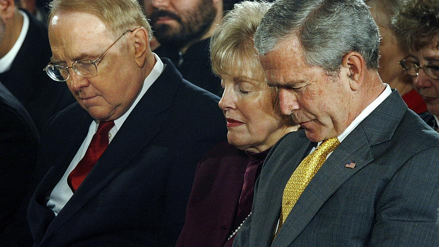 Image: President George W. Bush bows his head in prayer along with Dr. Jame