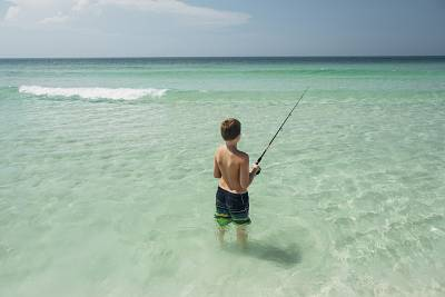 A boy fishes off the cost of Pensacola Beach, Florida.