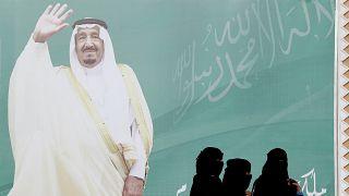 Image: FILE PHOTO: Women walk past a poster of Saudi Arabia's King Salman b