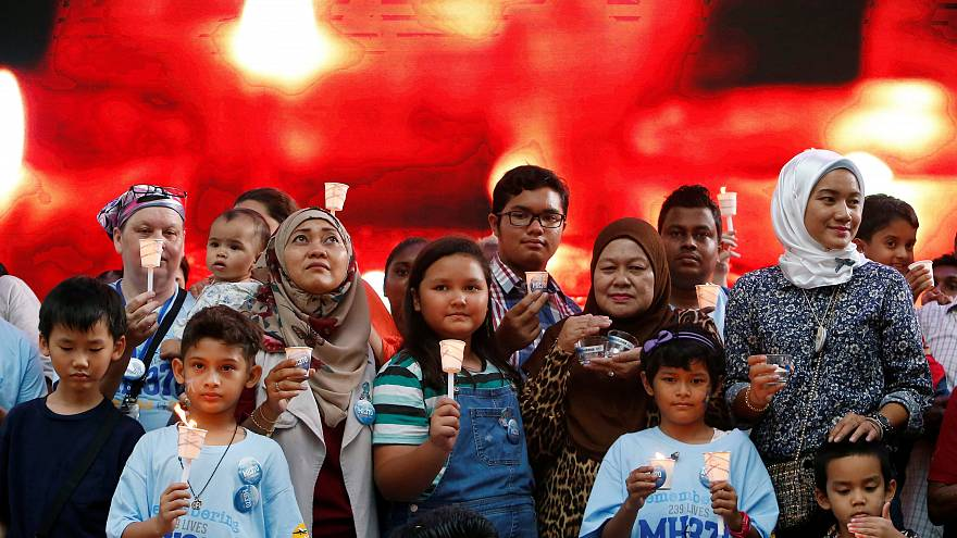 Image: Family members hold candles during the fifth annual remembrance even
