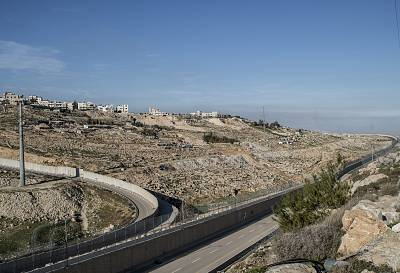 A fence sits on the high concrete wall running down the middle of Route 4370, slicing the road in two: The far lane is for Israeli-registered vehicles, the other for Palestinian traffic and cannot enter Jerusalem.