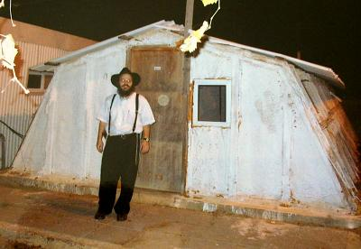 Shabtay Bendet stands in front of a makeshift building in the West Bank settlement of Rechalim in 2002.