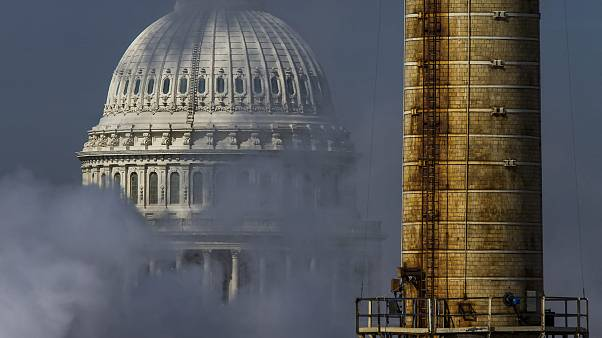 Image: The dome of the U.S. Capitol is seen behind the smokestack from the