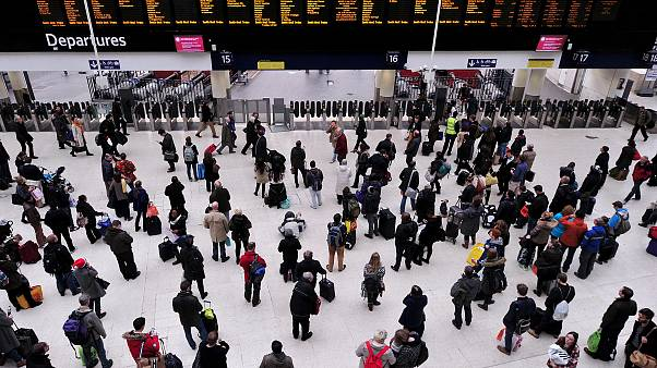 Image: Travelers wait near the departure boards at London's Waterloo train