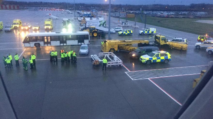 Image: Emergency personnel wait for passengers to disembark a flight from B