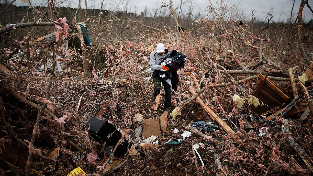 Image: Dax Leandro salvages clothing from the wreckage of his friend's home