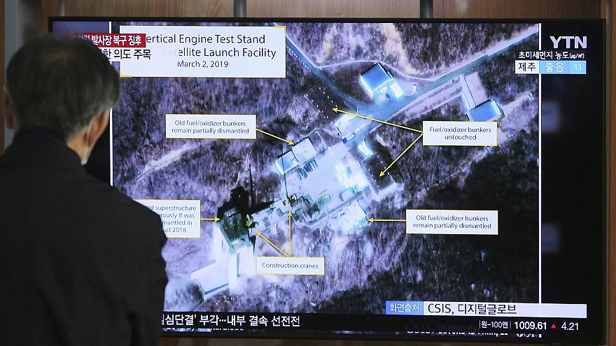 Image: A man watches a TV screen showing an image of the Sohae Satellite La