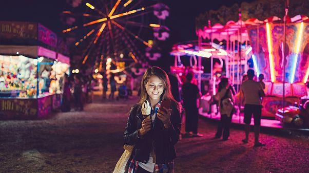 Image: Smiling woman texting at the amusement park
