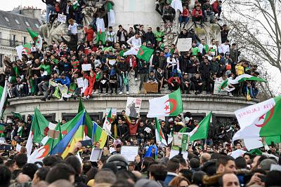 Protesters wave Algerian and Berber flags during a rally in support of the ongoing protests in Algeria against the president\'s bid for a fifth term in power, at Place de la Republique in Paris, on March 10, 2019.
