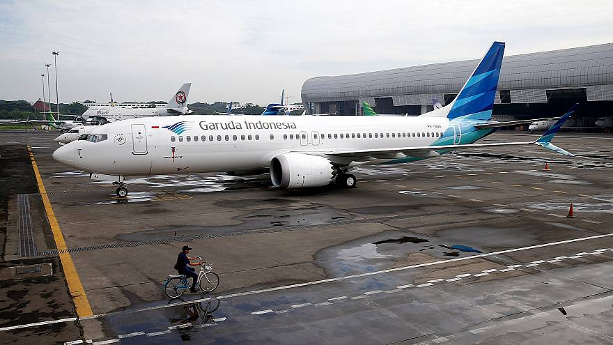 Image: An official rides a bicycle as he passes Garuda Indonesia's Boeing 7