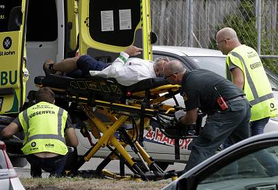 Ambulance staff take a man from outside a mosque in central Christchurch.