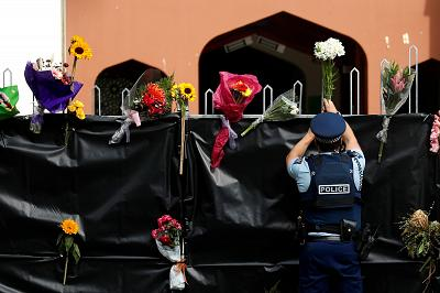 A police officer places flowers at the entrance of Masjid Al Noor mosque in Christchurch, New Zealand on March 17, 2019.