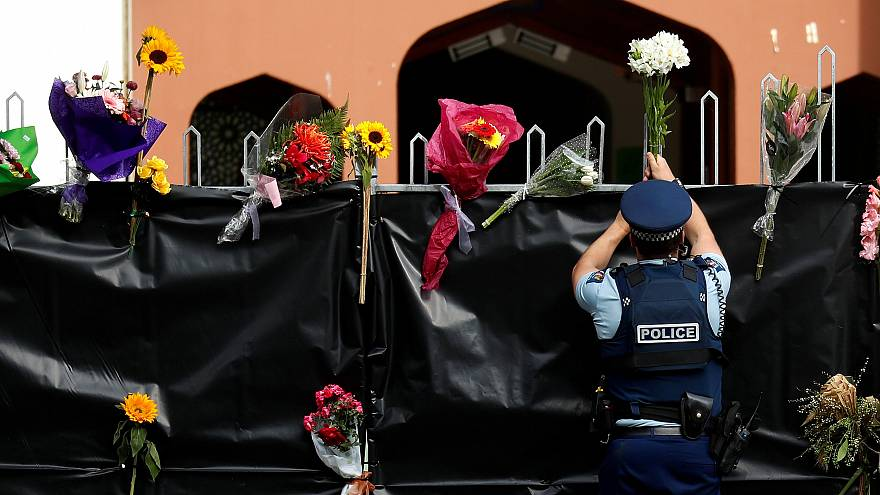 Image: A police officer places flowers at the entrance of Masjid Al Noor mo
