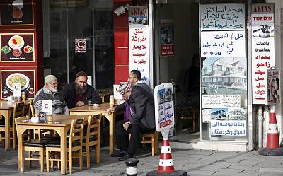 Men chat in front of a real estate agency in Istanbul which has Arabic notices on its window.