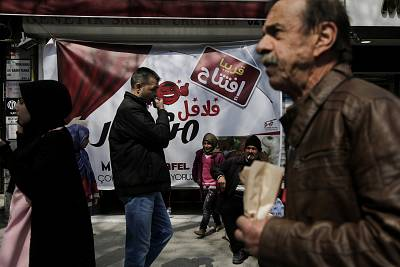 "Passersby walk past an Arabic sign for a falafel shop in Istanbul\'s ""Little Syria"" neighborhood."