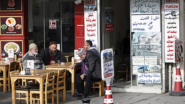 Image: Men chat in front of a real estate agency in Istanbul which has Arab