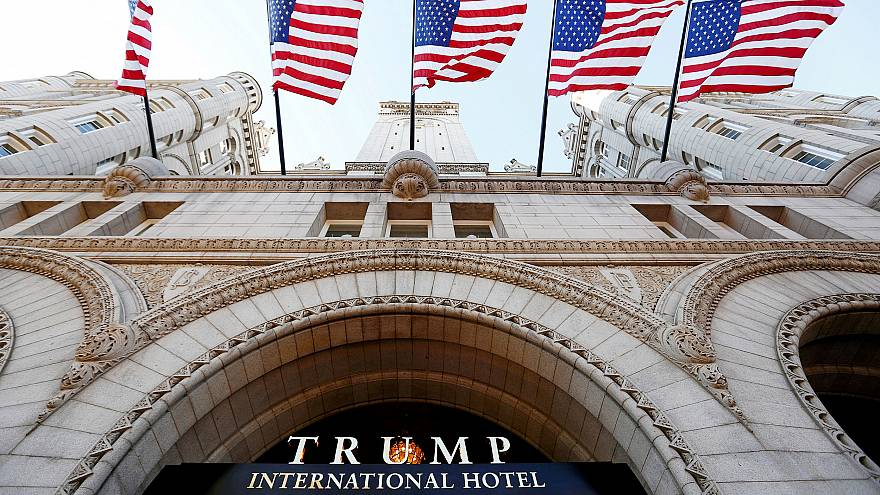 Image: Flags fly above the entrance to the new Trump International Hotel on