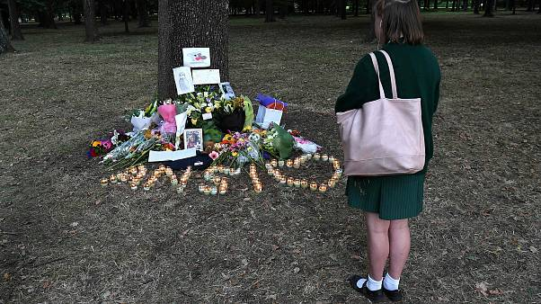 Image: A student pays respect at a memorial site for the victims of mosque