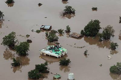 People on a roof surrounded by flooding in an area affected by Cyclone Idai in Beira, Mozambique.