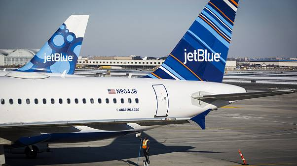 An airport worker fuels a JetBlue plane on the tarmac of the John F. Kenned