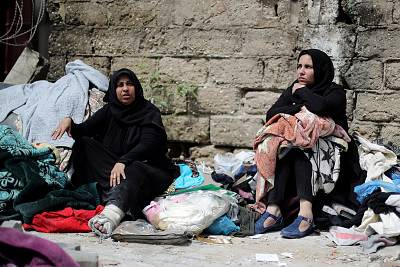 Palestinians sit with their belongings in a street outside their destroyed house after an Israeli missile targeted a nearby Hamas site in Gaza City.