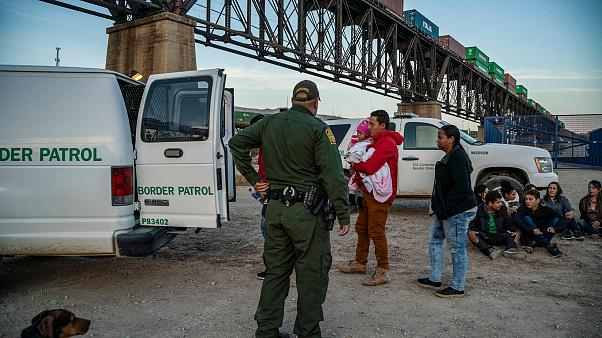Image: A group of Brazilian migrants board a US Border Patrol van in Sunlan