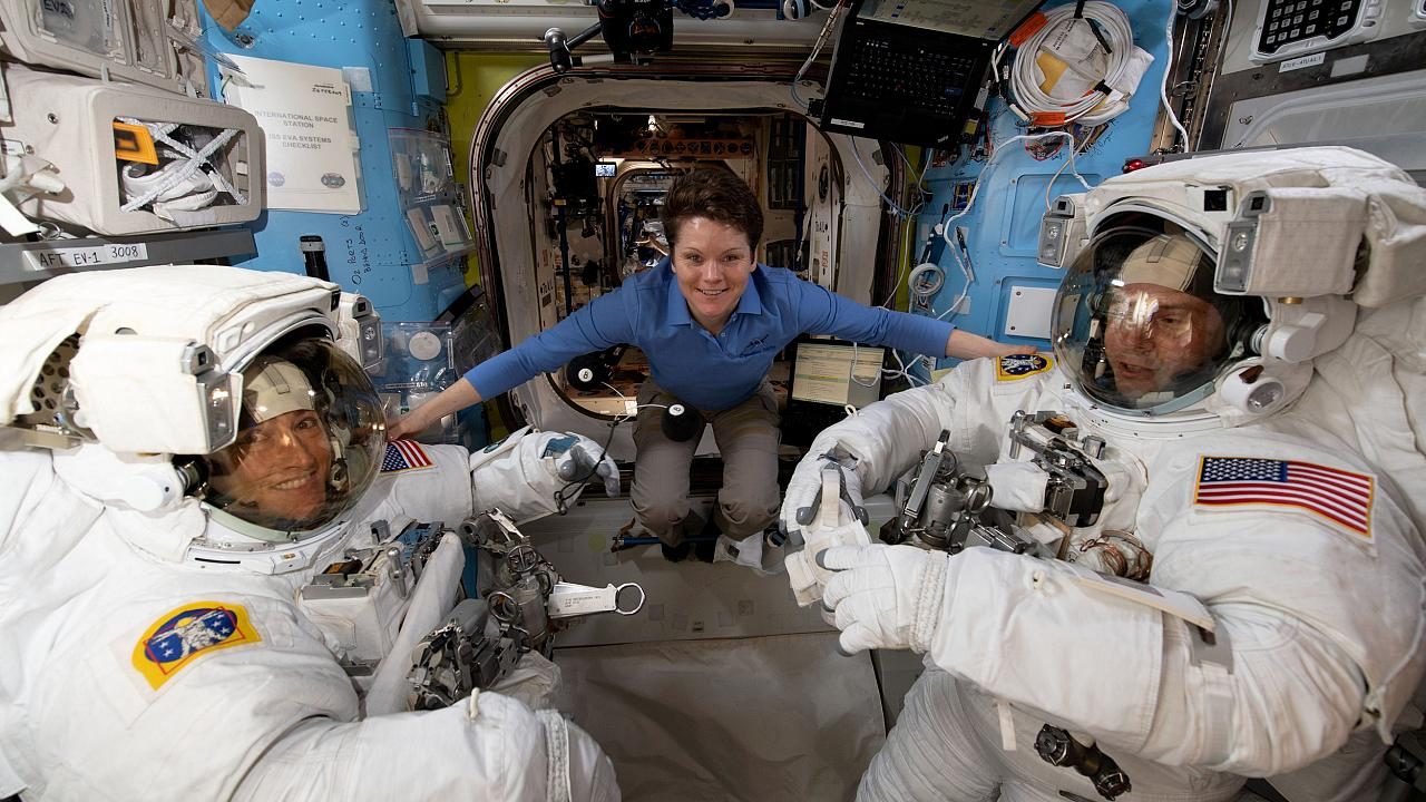 Image: NASA astronaut Anne McClain assists fellow astronauts Christina Koch