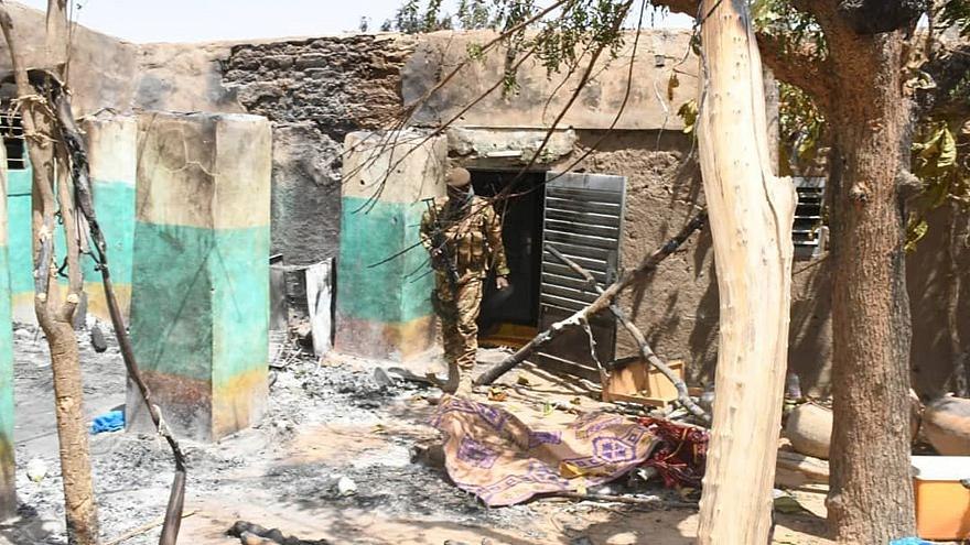 Image: A soldier walks amid the damage after an attack by gunmen on Fulani