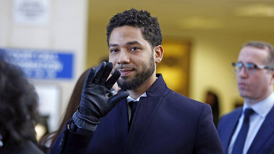 Image: Actor Jussie Smollett waves as he follows his attorney to the microp