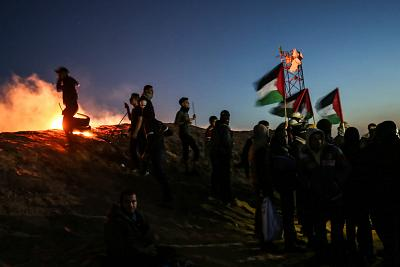Palestinians protest near the fence along the border with Israel on March 19, 2019.