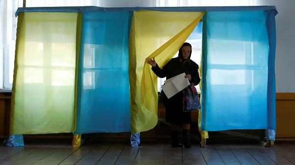 Image: A woman walks out of a voting booth at a polling station during a pr