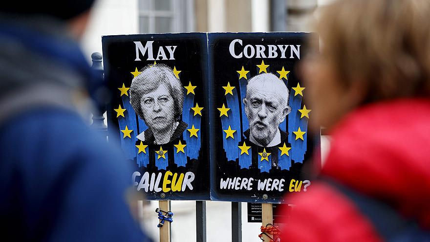 Image: Pedestrians walk past placards featuring Britain's Prime Minister Th