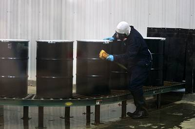 A worker decontaminates steel drums containing yellowcake uranium to ensure safe shipment at UR Energy\'s Lost Creek uranium production facility in Sweetwater County, Wyo., on Dec. 9, 2013.