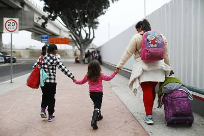 A migrant mother walks with her two daughters on their way to the port of entry to ask for asylum in the U.S. last June in Tijuana, Mexico.
